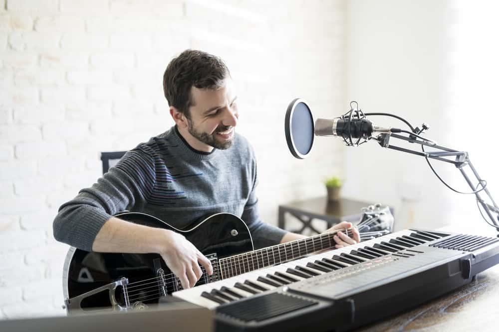 Handsome hispanic man enjoying playing guitar at radio station, playing music live on air and smiling.