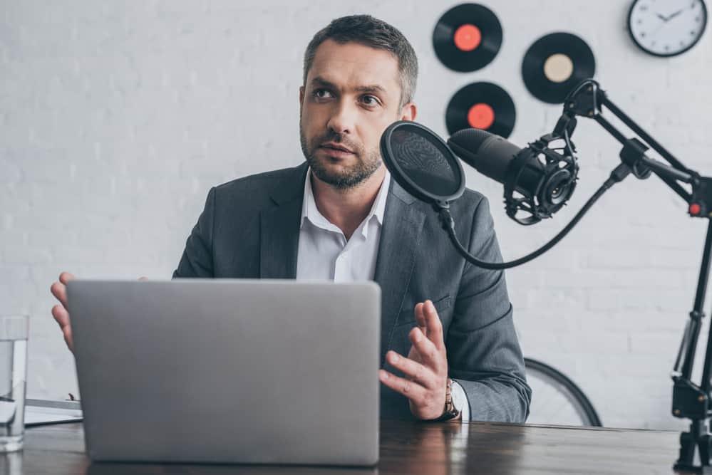 Handsome radio host gesturing while speaking in microphone