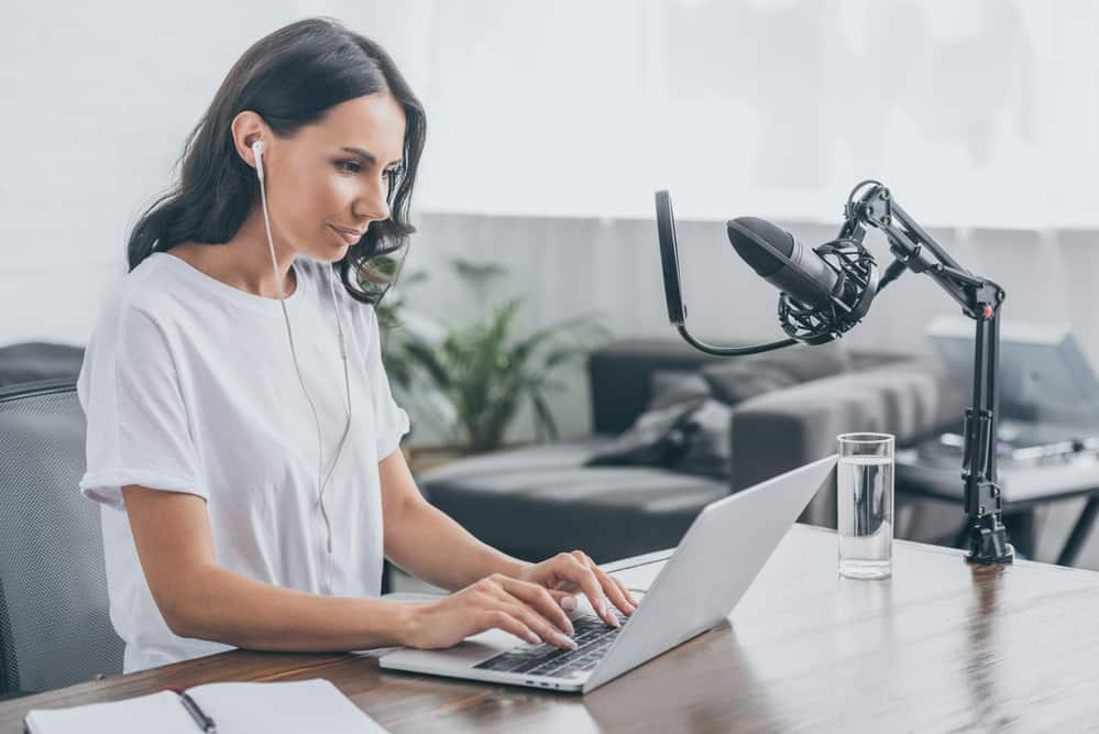 Pretty radio host in earphones using laptop while sitting
