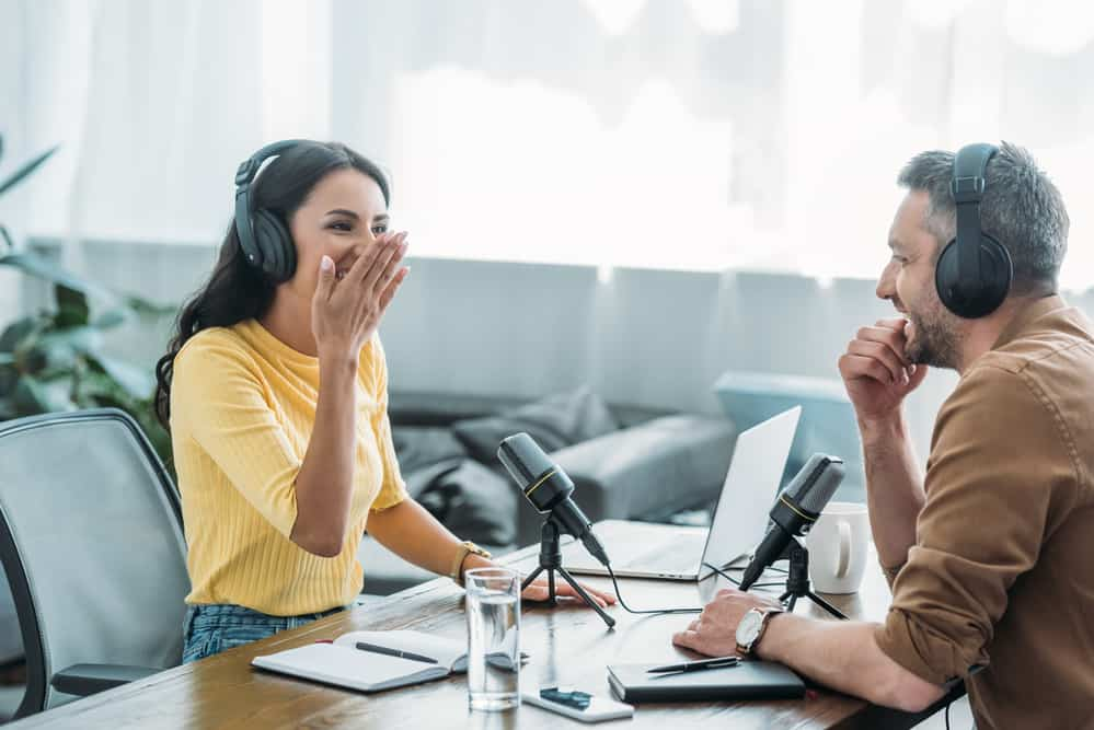 Pretty radio host laughing while recording podcast
