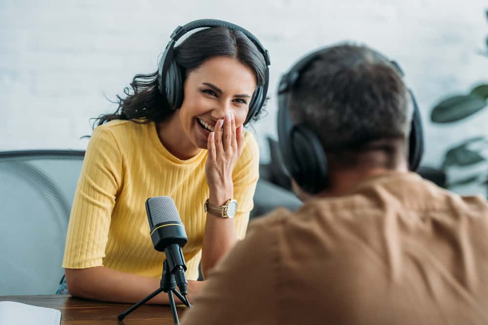 Selective focus of cheerful radio host laughing while recording