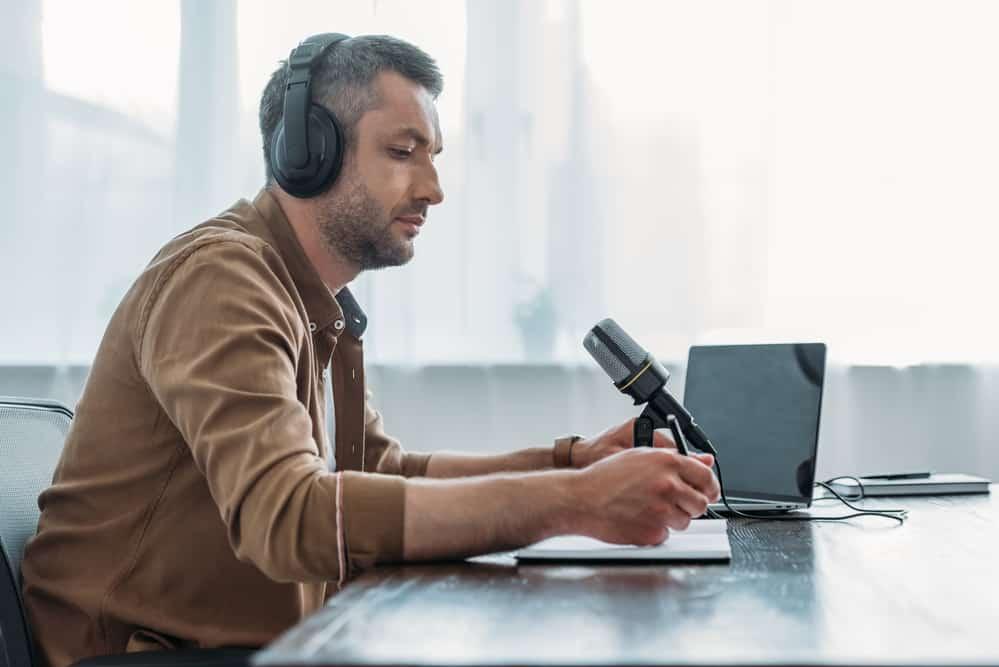 Serious radio host in headphones sitting near microphone