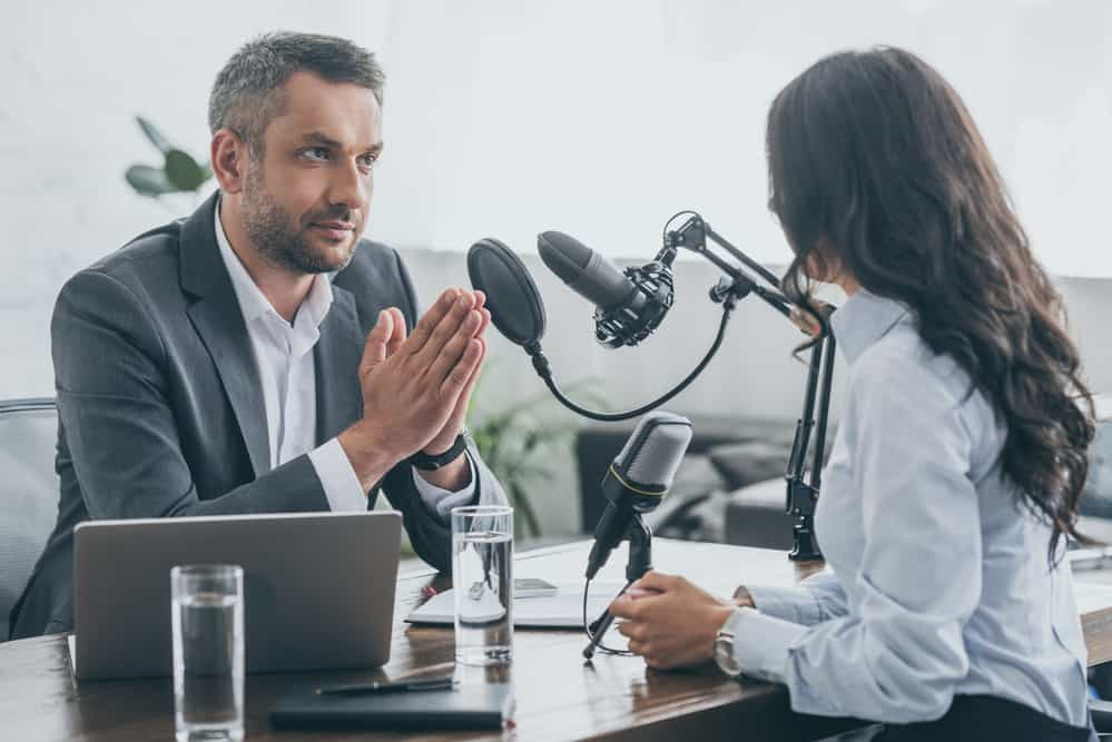 Serious radio host interviewing young businesswoman
