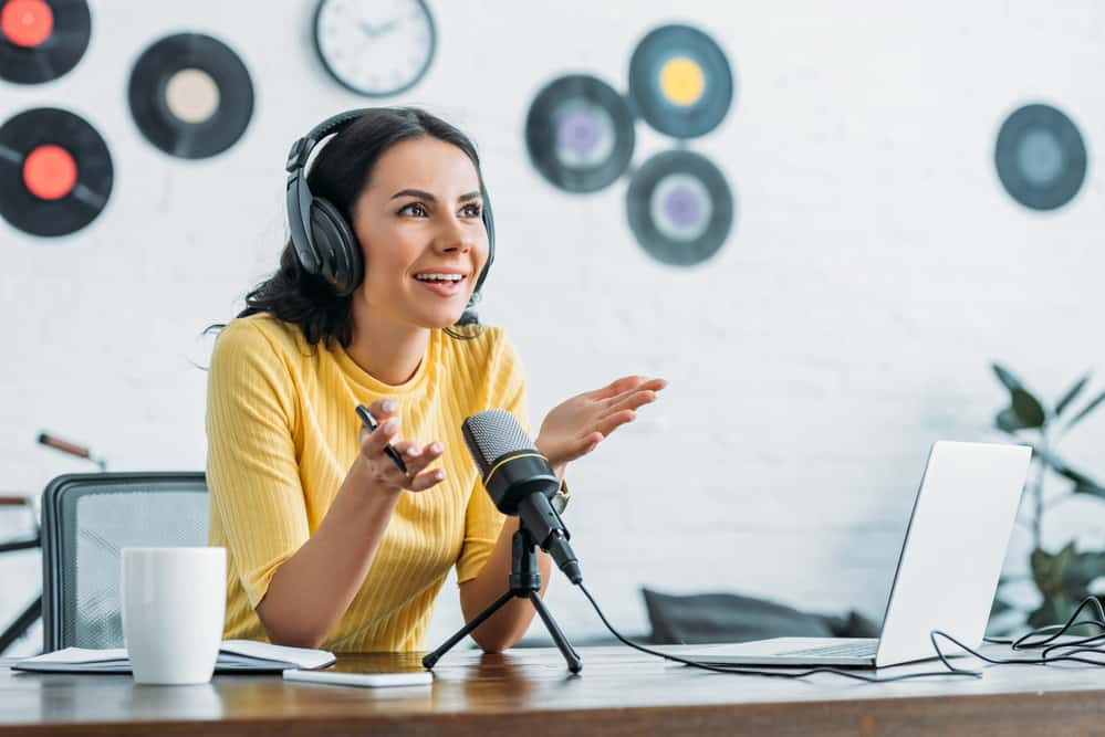 Smiling radio host gesturing while recording podcast