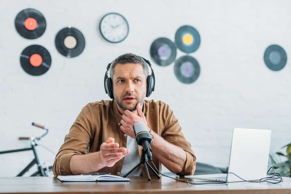 Thoughtful radio host in headphones recording podcast