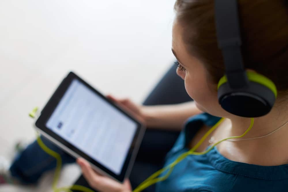 Beautiful woman relaxes on sofa and watches podcast on tablet pc, listening with green big earphones. Copy space